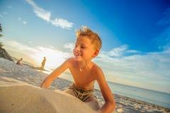 Hübsche acht Jahre Junge auf Strand führt die akrobatischen Skizzen durch Lizenzfreie Stockfotos