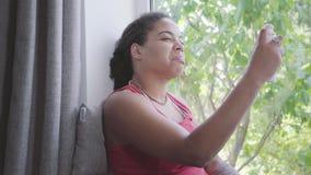 Hübsche Afroamerikanerfrau, die auf der Fensterbrettnahaufnahme sitzt Das Mädchen sprüht Kosmetik auf im Gesicht stock video