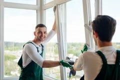 Hübsche Arbeitskraft, die ein Fenster installiert lizenzfreies stockfoto