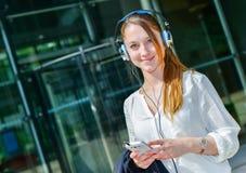 Hübsche Arbeitskraft, die Musik in der Front ihre Firma hört Lizenzfreie Stockfotografie