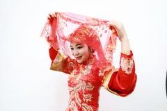 Hübsche asiatische chinesische schöne Braut mit traditionellem chinesischem rotem Kleid der Hochzeit und roten Hauptabdeckungen stockfotografie