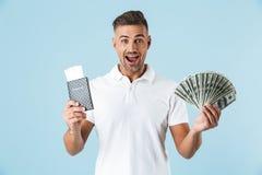 Hübsche aufgeregte emotionale erwachsene Mannaufstellung lokalisiert über blauem Wandhintergrund-Holdingpaß mit Karten und Geld stockbild