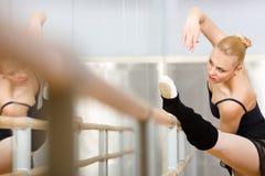 Hübsche Ballerina dehnt sich nahe Barre aus Lizenzfreie Stockfotos