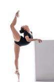 Hübsche Ballerina führt Vertikalenspalte im Tanz durch lizenzfreie stockfotografie