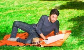 Hübsche Blicke des jungen Mannes überrascht im Park, der auf dem Gras mit einem Laptop sitzt Lizenzfreies Stockbild