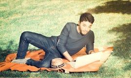 Hübsche Blicke des jungen Mannes überrascht im Park, der auf dem Gras mit einem Laptop, Weinleseeffekt sitzt Lizenzfreie Stockbilder