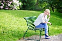 Hübsche blonde Frau auf der Bank, die Kamera betrachtet Lizenzfreie Stockbilder