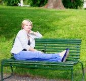 Hübsche blonde Frau, die auf Bank am Garten sitzt Stockfotos