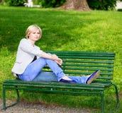 Hübsche blonde Frau, die auf Bank sitzt Lizenzfreies Stockfoto