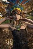 Hübsche blonde tragende Krone gemacht von den Federn des Pfaus stockbild