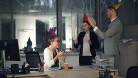 Hübsche Blondine arbeitet im modernen Büro, wenn ihre Kollegen Geburtstagskuchen, Geschenk und Parteihüte holen, Mädchen stock footage