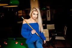 Hübsche Blondine, die mit dem Stichwort am Billardtisch aufwerfen Lizenzfreie Stockbilder