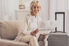 Hübsche Blondine, die nahe ihrem Gepäck sitzen lizenzfreie stockfotografie