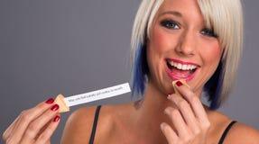 Hübsche Blondine essen den Glückskeks, der Mitteilung zeigt Stockfotografie