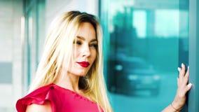 Hübsche Blondine im hellen Ausstattungstanzen nahe moderner errichtender Außenseite stock video