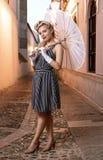 Hübsche Blondine im Retrostil, der mit einem japanischen Regenschirm aufwirft lizenzfreie stockbilder