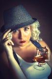 Hübsche Blondine in trinkendem Kognak des Hutes, Geschäftsart lizenzfreie stockfotos