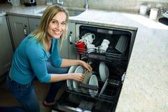 Hübsche Blondine, welche die Spülmaschine leeren lizenzfreie stockfotografie