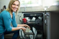 Hübsche Blondine, welche die Spülmaschine leeren lizenzfreie stockbilder