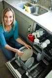 Hübsche Blondine, welche die Spülmaschine leeren lizenzfreies stockbild