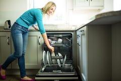 Hübsche Blondine, welche die Spülmaschine leeren stockfoto