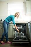 Hübsche Blondine, welche die Spülmaschine leeren stockfotografie