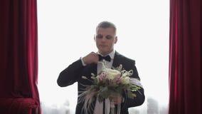 Hübsche Bräutigamstellung nahe Fenster mit einem Bündel Heiratsblumen Fokus auf dem Vordergrund Langsame Bewegung stock video