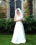 Hübsche Braut auf Rasen der Kirche Lizenzfreie Stockfotos