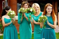 Hübsche Brautjungfern in den tadellosen Kleidern applaudieren während der Zeremonie lizenzfreie stockfotos