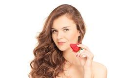 Hübsche Brunettefrau, die eine Erdbeere hält Stockbilder