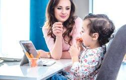 Hübsche Brunettefrau, die ihr Kind einzieht lizenzfreie stockbilder