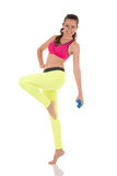Hübsche Brunettefrau, die zurück komplexe Übungen für Muskeln, Beine, Hinterteile und Hände unter Verwendung der blauen Dummköpfe Lizenzfreie Stockbilder