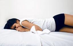 Hübsche Brunettefrau im Bett, schräger Schlaf Lizenzfreie Stockbilder
