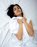 Hübsche Brunettefrau im Bett, schräger Schlaf Stockfotos