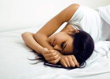 Hübsche Brunettefrau im Bett, schräger Schlaf Stockbilder