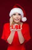 Hübsche Dame in der Weihnachtsschutzkappe übergibt ein Geschenk stockbild