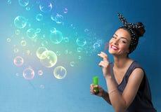 Hübsche Dame, die bunte Blasen auf blauem Hintergrund durchbrennt Stockfotos