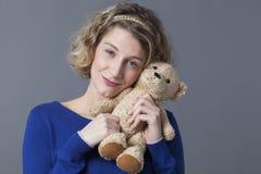 Hübsche Dame, die das knuddelige Spielzeug sich erinnert an Kindheit hält Lizenzfreie Stockfotografie