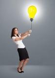 Hübsche Dame, die einen Glühlampeballon anhält Lizenzfreie Stockbilder