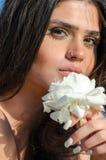 Hübsche Dame, die Front ihres Gesichtes eine große Weißrose hält Stockbilder