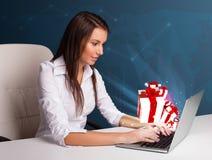 Hübsche Dame, die am Schreibtisch sitzt und auf Laptop mit anwesendem BO schreibt Lizenzfreie Stockfotos