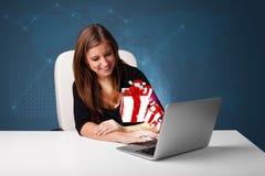 Hübsche Dame, die am Schreibtisch sitzt und auf Laptop mit anwesendem BO schreibt Lizenzfreie Stockbilder