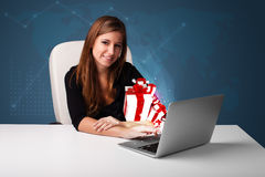 Hübsche Dame, die am Schreibtisch sitzt und auf Laptop mit anwesendem BO schreibt Stockfotos