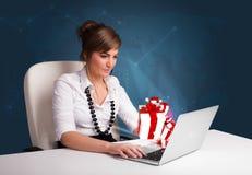 Hübsche Dame, die am Schreibtisch sitzt und auf Laptop mit anwesendem BO schreibt Stockbild