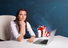 Hübsche Dame, die am Schreibtisch sitzt und auf Laptop mit anwesendem BO schreibt Stockfotografie