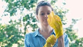 Hübsche Dame im blauen weißen Hemd setzt sich auf gelbe Gummihandschuhe stock video