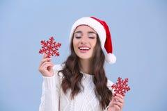 Hübsche Dame im Weihnachtshut, der rote Schneeflocken hält Lizenzfreie Stockbilder