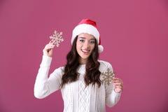 Hübsche Dame im Weihnachtshut, der Schneeflocken hält Stockfotos