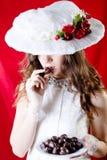 Hübsche Dame mit dem langen Haar im Retro- Hut und im Kleid Lizenzfreie Stockfotos