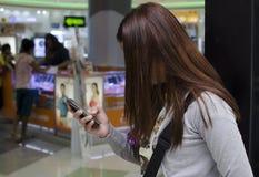 Hübsche Damenhaare umfasst Gesichtsversenden von sms-nachrichten mit Smartphone innerhalb des Kaufhauses stockfotografie